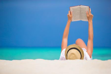 젊은 여자는 열 대 하얀 해변에 읽고