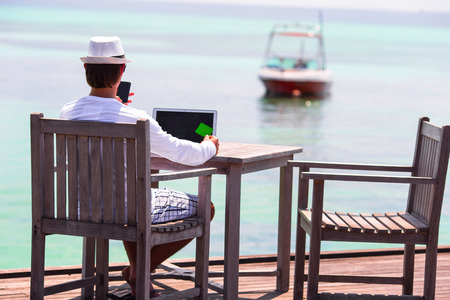business trip: Young man with tablet computer and cell phone on tropical beach Stock Photo