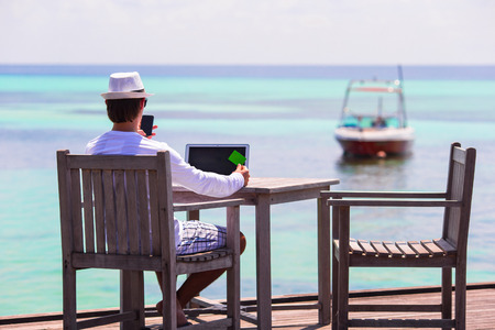 Young man with tablet computer and cell phone on tropical beach Banque d'images