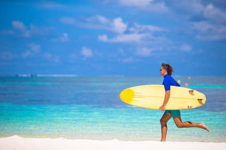 Happy young surf man runing at the beach with a surfboard