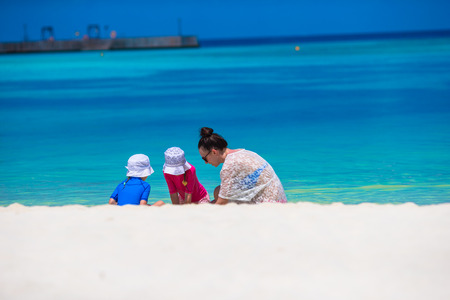 Young mom and little girls playing on white sandy beach photo