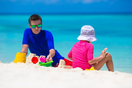 Adorable little girl and happy father playing with beach toys on summer vacation photo