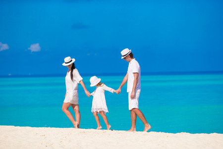 Young parent and little kid on white tropical beach photo
