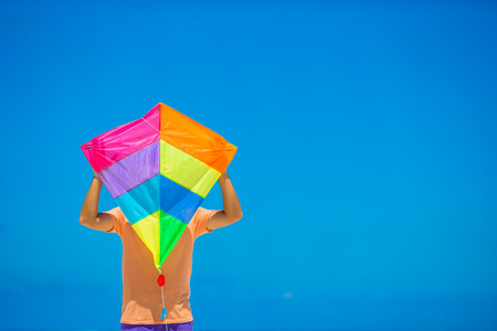 kite: Young man with a kite on a background of turquoise sea