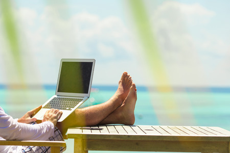 Young man with tablet computer during tropical beach vacation 스톡 콘텐츠