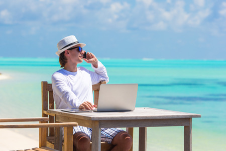 Young man with tablet computer and cell phone on tropical beach 版權商用圖片