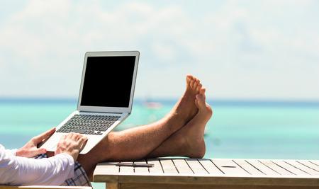 Hombre joven con tablet PC durante las vacaciones de playa tropical