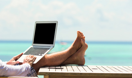 Young man with tablet computer during tropical beach vacation Stockfoto