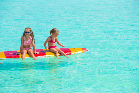young girl bikini: Little adorable girls on a surfboard in the turquoise sea