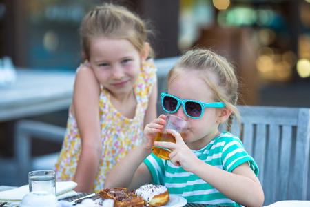 honey blonde: Adorable little girls having breakfast at outdoor cafe Stock Photo
