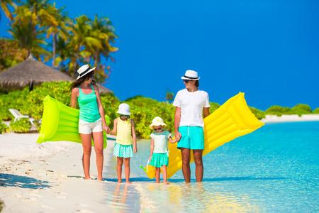 Happy family of four on white beach