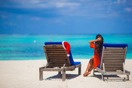 longue: Red santa hat on chair longue at tropical white beach Stock Photo