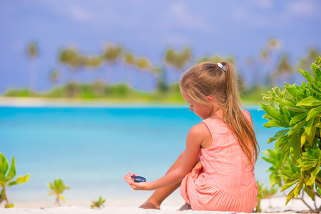azimuth: Little girl traveler with a compass in the hand on the beach Stock Photo