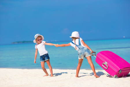 portmanteau: Little adorable girls with big suitcase on tropical white beach