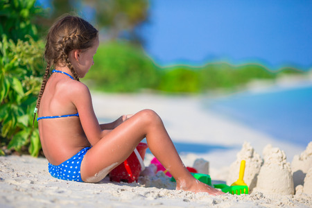 children sandcastle: Adorable little girl playing with beach toys during tropical vacation Stock Photo