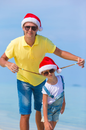 Little girl and happy dad in Santa Hat during beach vacation photo