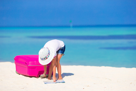 portmanteau: Little adorable girl with big suitcase on tropical white beach Stock Photo