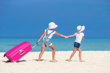 portmanteau: Little tourists girls with big suitcase on tropical white beach