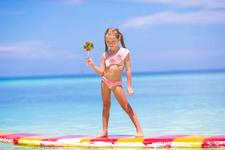 paletas de caramelo: Ni�a con el lollipop divertirse en tabla de surf en el mar