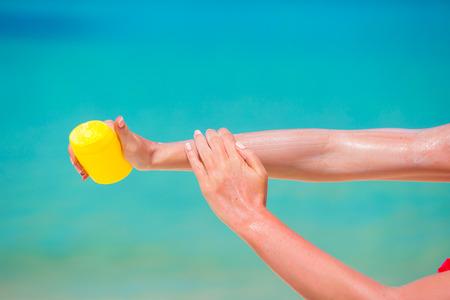 suncream: Female hands with suncream bottle background blue sea Stock Photo