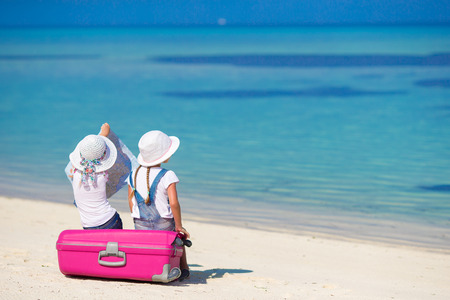 portmanteau: Little girls with big suitcase and map at tropical beach