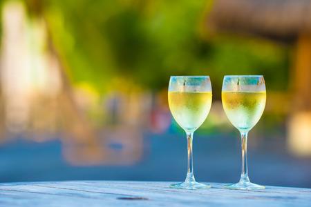 copa de vino: Dos vasos de vino blanco sabroso en la puesta en mesa de madera