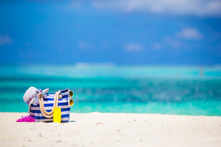 Stripe bag, blue towel, sunglasses, sunscreen bottle and swimsuit on white beach