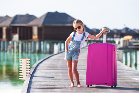 portmanteau: Little adorable girl with big luggage on wooden jetty on her way to water bungalow during summer vacation