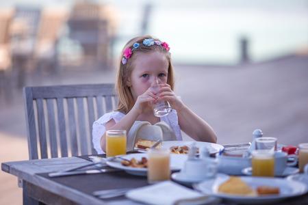 honey blonde: Adorable little girl having breakfast at outdoor cafe Stock Photo