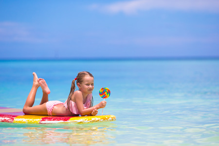 little girl posing: Little girl with lollipop have fun on surfboard in the sea
