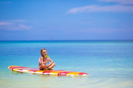 yellow bikini: Little girl with lollipop have fun on surfboard in the sea