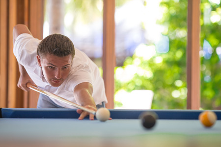 snooker halls: Young man playing billiards on summer vacation Stock Photo