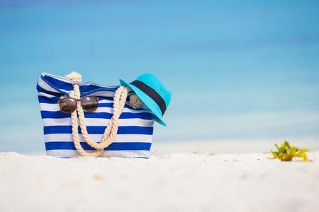 Beach accessories - blue bag, straw hat, sunglasses on white beach photo