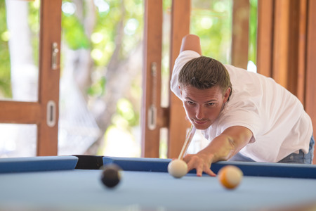 billiards halls: Young man playing billiards on summer vacation Stock Photo