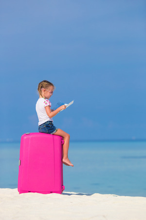 portmanteau: Little adorable girl with big pink suitcase and map of island on white beach