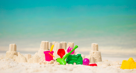 sandcastle: Sandcastle at white beach with plastic kids toys