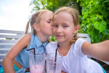 Little girls taking selfie and drinking tasty cocktails at outdoor cafe photo