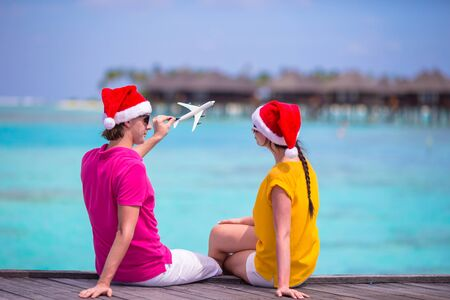 Young couple in Santa hats relaxing on wooden jetty on Christmas vacation photo