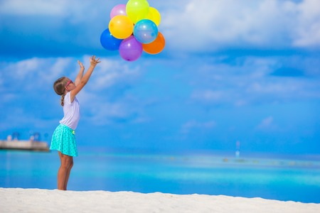 little girl beach: Adorable little girl playing with colorful balloons at tropical beach Stock Photo