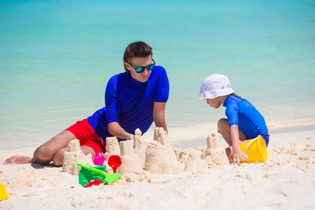 Happy family playing with beach toys on summer vacation photo