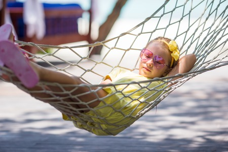 Little girl on tropical vacation relaxing in hammock photo