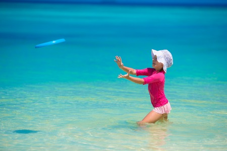 little girl swimsuit: Little girl playing with flying disc at white beach Stock Photo