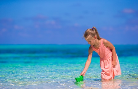 Adorable little girl playing with origami boat in turquoise sea photo