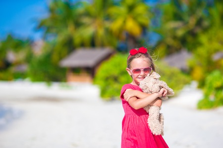 plush toy: Adorable little girl playing with plush toy on beach