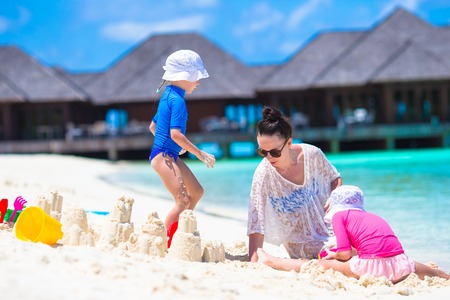 Adorable little girls and happy mother playing with beach toys on summer vacation photo