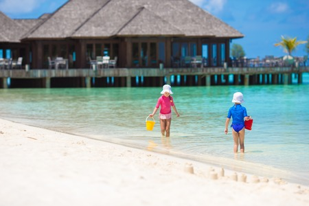 Adorable little girls at beach during summer vacation photo