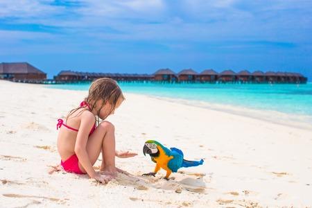 cotorra: Niña adorable en la playa con el loro colorido grande