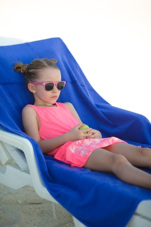 youngbaby: Adorable little girl sitting on chair at tropical beach Stock Photo