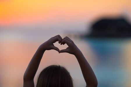 happines: Silhouette of heart made by kids hand at sunset