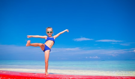 little girl posing: Little adorable girl on a surfboard in the turquoise sea Stock Photo